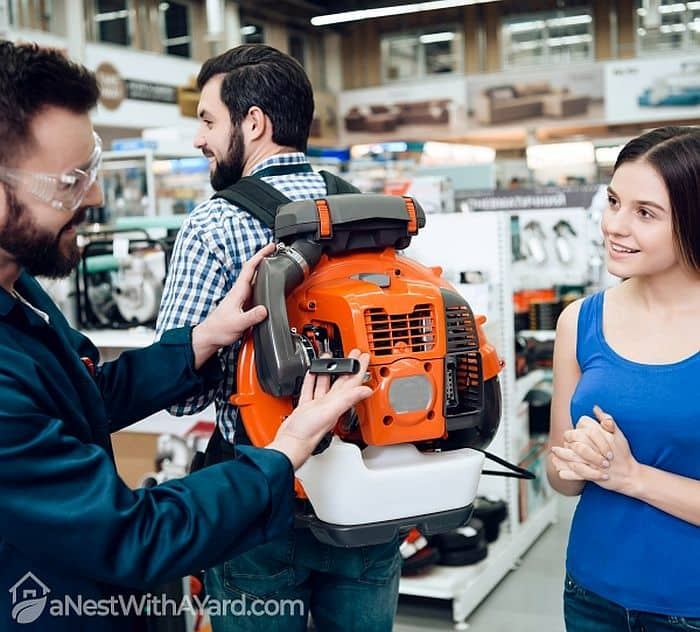 A male salesman  explaining the features of a back pack leaf blower to a potential buyer