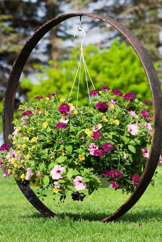 A hanging flower planter in the middle of a lawn  #smallGarden #SmallGardenDesign #smallyardlandscaping #gardenIdeas #backyardLandscaping #backyardLandscapingIdeas #landscaping