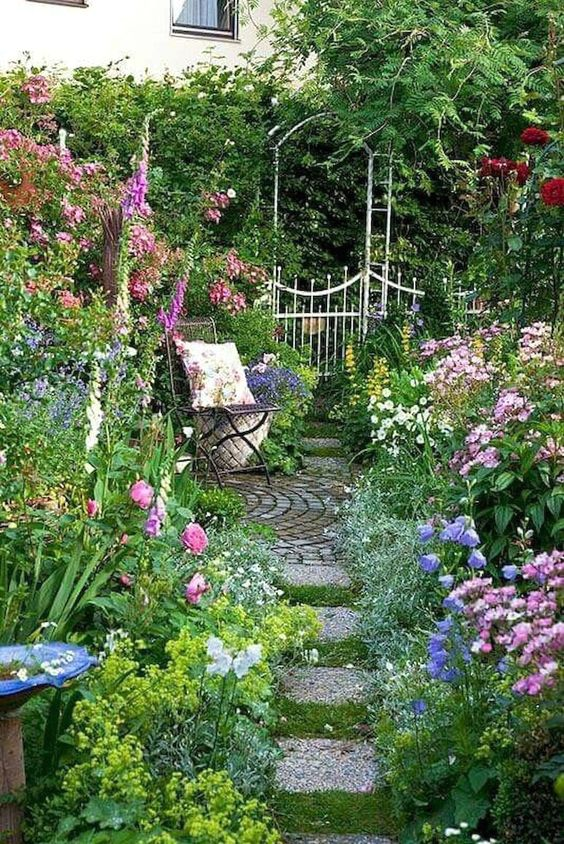 A small blooming garden with a chair  #smallGarden #SmallGardenDesign #smallyardlandscaping #gardenIdeas #backyardLandscaping #backyardLandscapingIdeas #landscaping