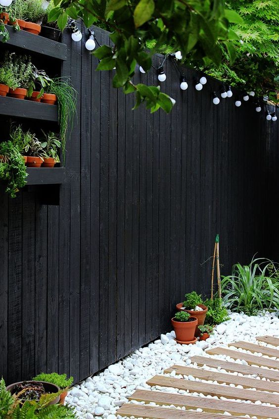 A small garden with plants in containers near a fence  #smallGarden #SmallGardenDesign #smallyardlandscaping #gardenIdeas #backyardLandscaping #backyardLandscapingIdeas #landscaping
