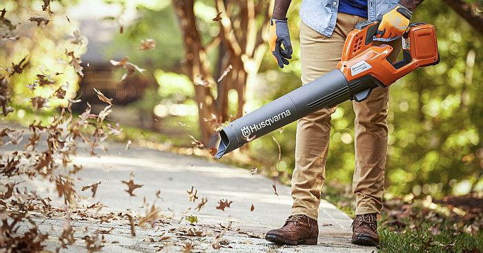 A handheld leaf blower blowing off fallen leaves from the pavement