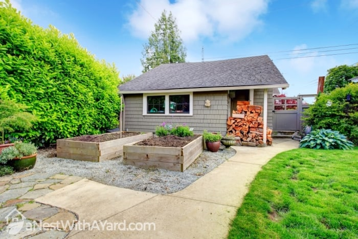 A picture of a shed with stacks of firewood in a backyard with with raised beds and and green grass lawn
