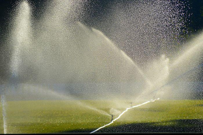 A series of water sprinklers sprinkling water on a big lawn