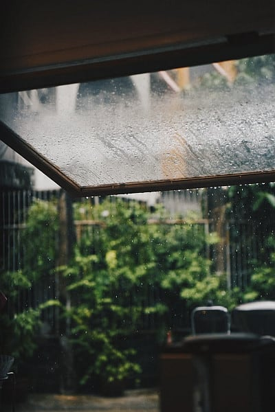 A shot of a pergolas roof with raindrops streaking through it