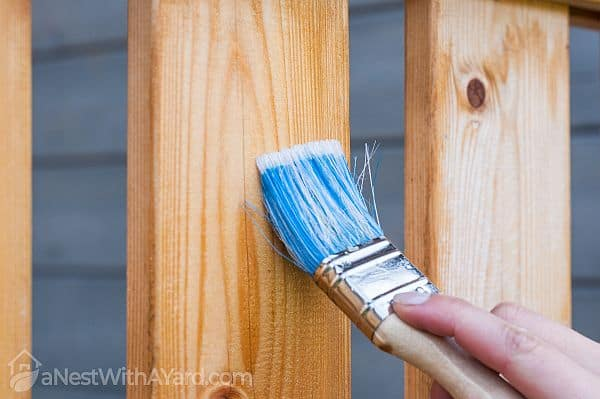 treating and sealing a wooden fence with a brush