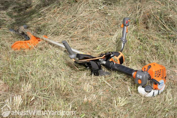 A brush cutter trimmer laying on the ground