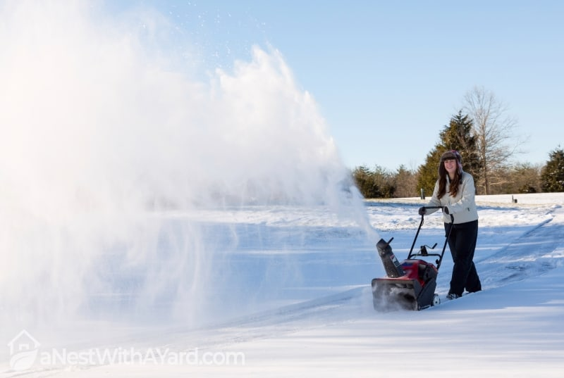 Young lady using a snowblower on rural drive on windy day with a cloud or blizzard of snow blowing in the air