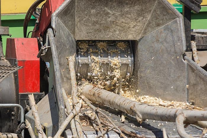 a shot of industrial wood chipper hopper with logs getting shredded in it