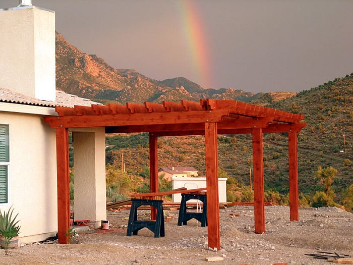 A picture of a pergola with a mountain and a rainbow in the background