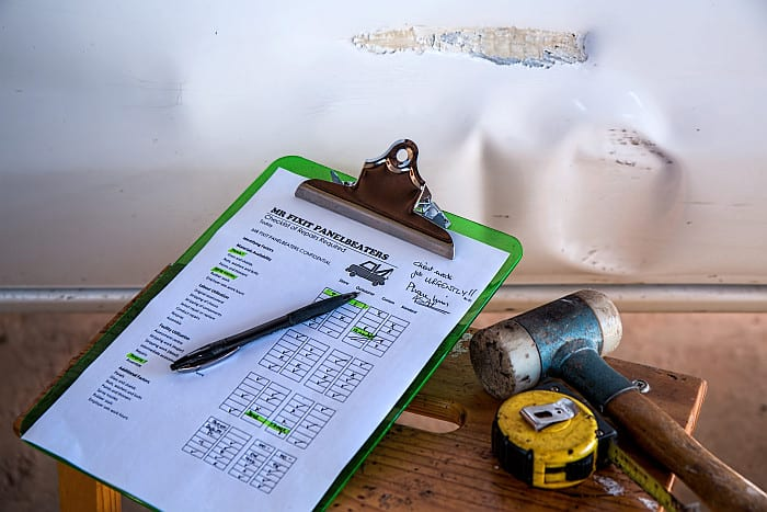 A picture of a checklist beside mallet and a tape measure upon a small table